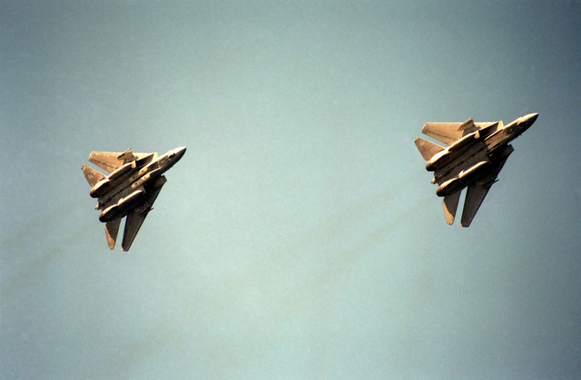 An underside view of two F-14A Tomcat aircraft in flight over the aircraft carrier USS SARATOGA (CV 60)
