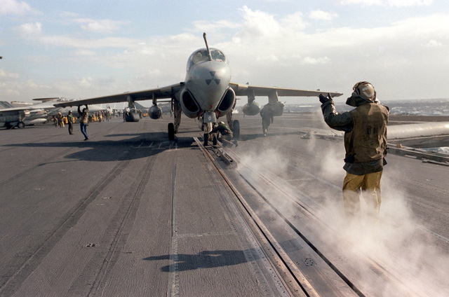 Catapult crewmen position an EA-6B Prowler aircraft on a catapult during flight operations aboard the aircraft carrier USS SARATOGA (CV 60)