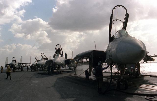 Crewman refuel F-14A Tomcat aircraft during flight operations aboard the aircraft carrier USS SARATOGA (CV 60)