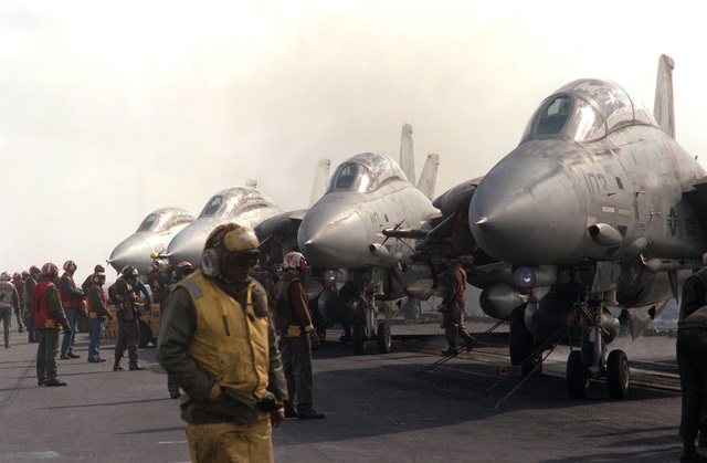 F-14A Tomcat aircraft parked on the deck of the aircraft carrier USS SARATOGA (CV 60) wait to be moved to the catapults for launch