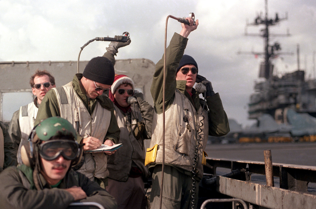 Landing signal officers aboard the aircraft carrier USS SARATOGA (CV 60) guide aircraft on approach for landing