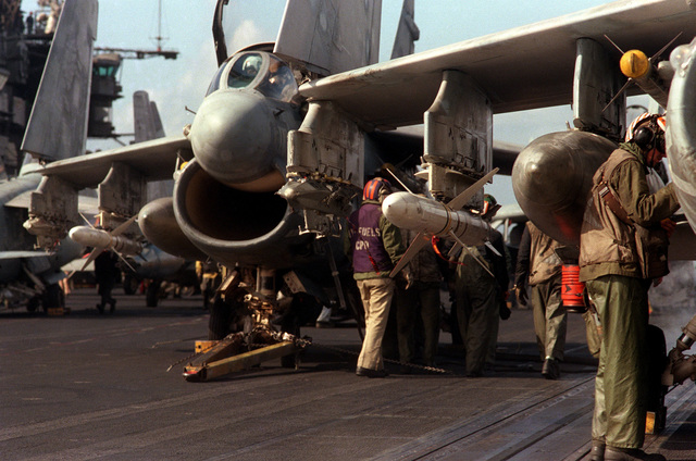 Preflight checks are conducted on A-7E II Corsair aircraft prior to flight operations aboard the aircraft carrier USS SARATOGA (CV 60). The aircraft in the foreground is armed with AIM-9 Sidewinder missile on the fuselage station and an AGM-45 Shrike missile on the right wing pylon