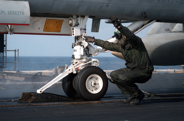 A catapult crewman checks the catapult connections on an F/A-18A Hornet aircraft prior to launching during flight operations aboard the aircraft carrier USS CORAL SEA (CV 43)