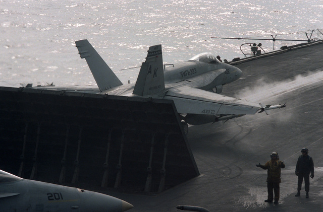 A jet blast deflector is raised behind an F/A-18A Hornet from Marine Fighter-Attack Squadron 323 during flight operations aboard the aircraft carrier USS CORAL SEA (CV 43)