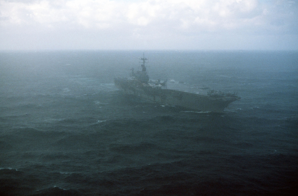 A starboard bow view of the aircraft carrier USS SARATOGA (CV 60) underway in foggy conditions