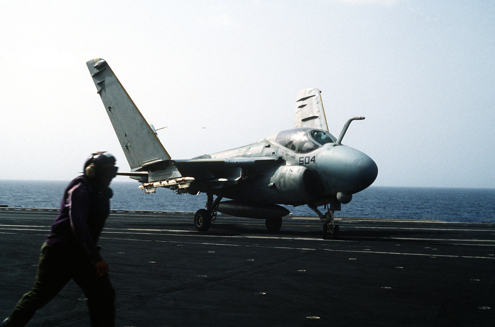An A-6E Intruder aircraft taxis on the flight deck of the aircraft carrier USS CORAL SEA (CV-43) shortly after landing