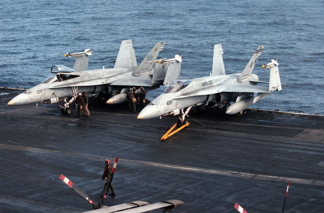 An F/A-18A Hornet aircraft from Strike-Fighter Squadron 131 and an F/A-18A from Marine Fighter-Attack Squadron 323 are parked on the edge of the flight deck during flight operations aboard the aircraft carrier USS CORAL SEA (CV-43). The aircraft are armed with ATM-9 Sidewinder air-to-air missiles on the wing tips