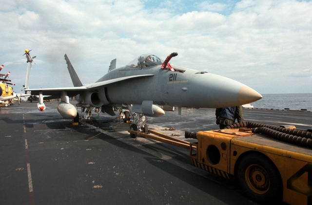 An MD-3A tow tractor is attached to an F/A-18A Hornet aircraft during flight operations aboard the aircraft carrier USS CORAL SEA (CV 43)