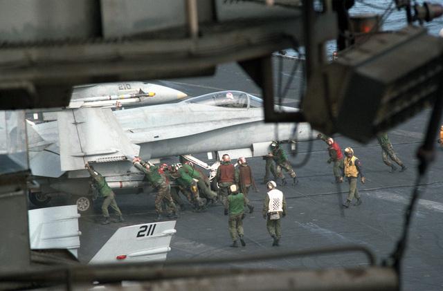 Flight deck crewmen maneuver an F/A-18A Hornet aircraft across the flight deck during flight operations aboard the aircraft carrier USS CORAL SEA (CV 43)