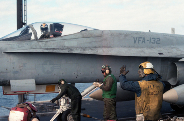 Flight deck crewmen prepare to launch an F/A-18A Hornet aircraft from Strike-Fighter Squadron 132 during flight operations aboard the aircraft carrier USS CORAL SEA (CV 43)