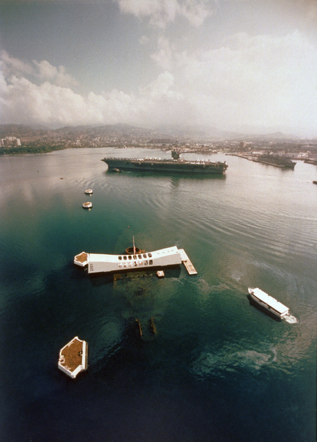 A port view of the nuclear-powered aircraft carrier USS ENTERPRISE (CVN 65) in Pearl Harbor. The ARIZONA Memorial is in the foreground. (SUBSTANDARD)