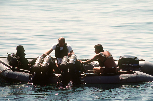 US Navy divers are helped aboard an inflatable boat by fellow divers during recovery operations for the space shuttle Challenger