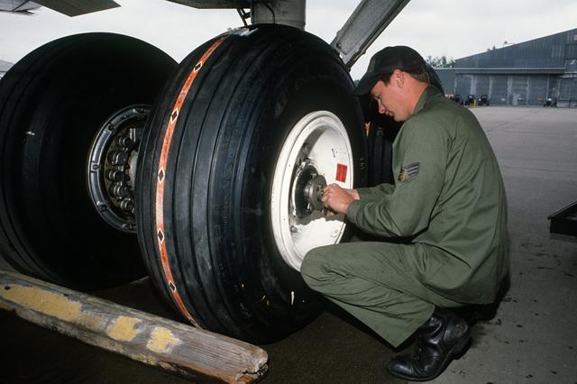 SENIOR AIRMAN (SRA) Stuart Turner checks a tire he just changed on a WC-135 Stratolifter aircraft