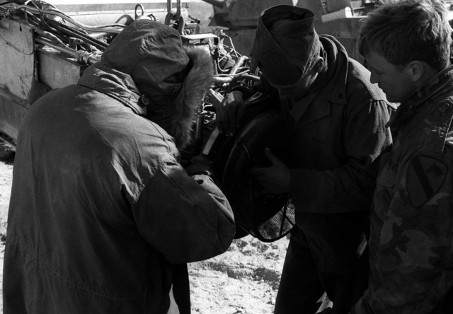Mechanics from the 1ST Cavalry Division remove a screen from the engine of an M-1A1 Abrams main battle tank in the field near Leach Lake during their unit's deployment to the National Training Center