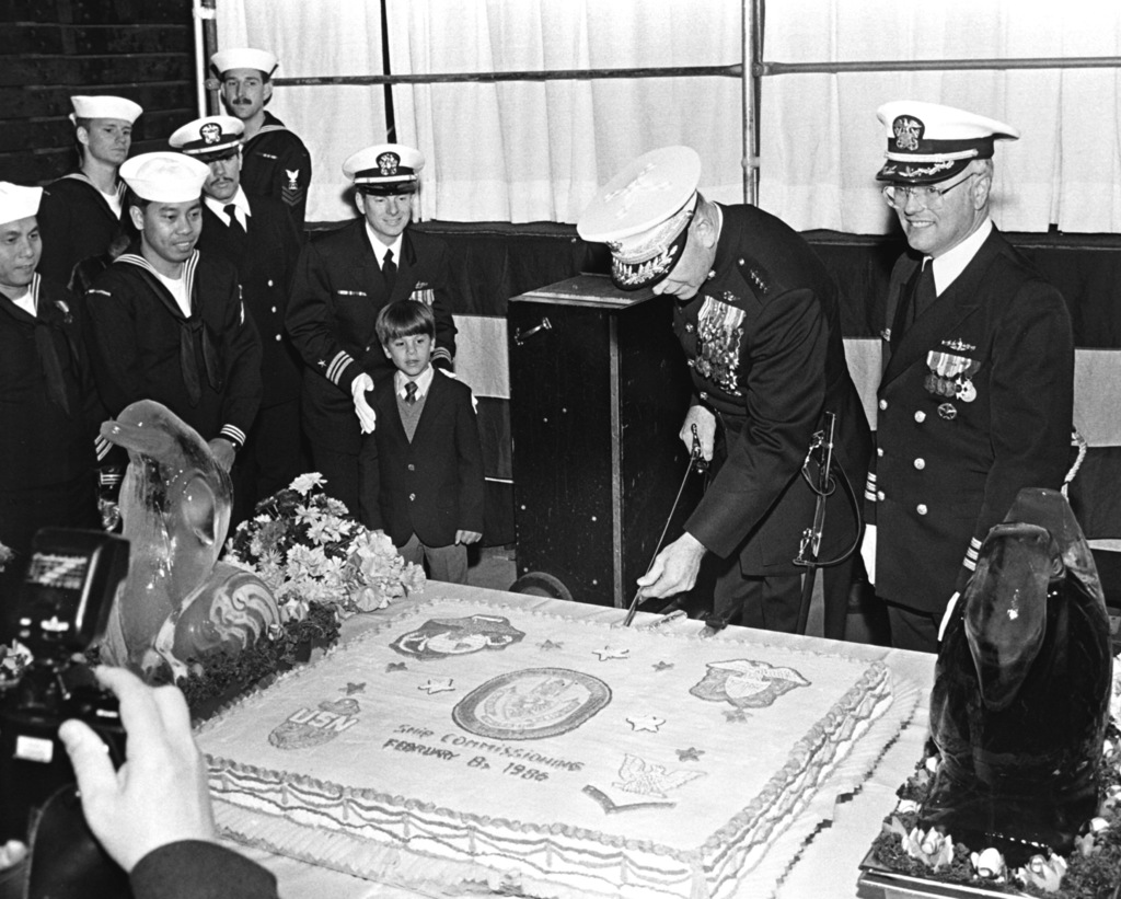 Crew members and guests watch as GEN. Paul X. Kelley, commandant of the Marine Corps, cuts the cake during the commissioning of the dock landing ship USS GERMANTOWN (LSD-42). On the right is CMDR. Edward M. Kline, commanding officer of the Germantown
