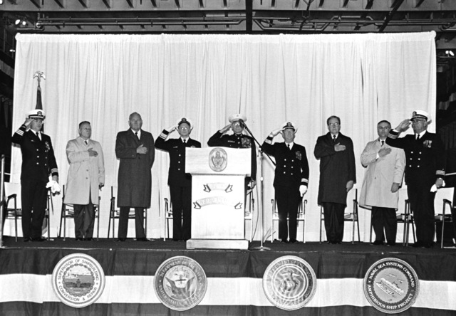 Distinguished guests honor the flag as the national anthem is played during the commissioning of the dock landing ship USS GERMANTOWN (LSD-42). See master caption for names of individuals present