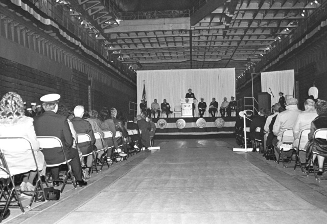 Guests seated in the well deck of the dock landing ship USS GERMANTOWN (LSD-42) listen as Rear Adm. Lavern S. Severance, commander, Naval Base, Seattle, deliveres an address during the ship's commissioning