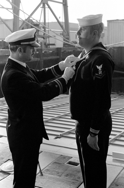 Lieutenant J. Craig inspects the appearance of Boatswain's Mate 2nd Class J. Anderson prior to the commissioning of the dock landing ship USS GERMANTOWN (LSD 42) at the Lockheed shipyard