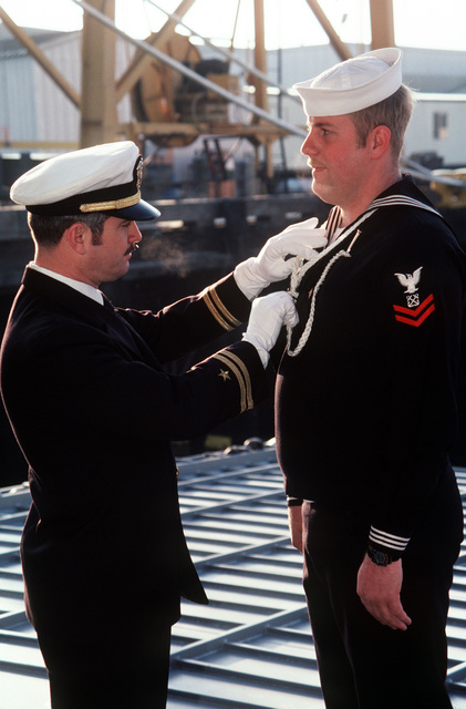 Lieutenant J. Craig inspects the appearance of Boatswain's Mate Second Class J. Anderson prior to the commissioning of the dock landing ship USS GERMANTOWN (LSD 42) at the Lockheed shipyard