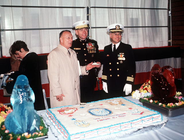 Retired Colonel (COL) Eugene E. Shoults, amphibious ship acquisition project manager, Naval Sea Systems Command; General (GEN) Paul X. Kelley, commandant of the Marine Corps; and Commander (CDR) Edward M. Kline, prospective commanding officer, pose with a cake at the commissioning of the dock landing ship USS GERMANTOWN (LSD 42) at the Lockheed shipyard