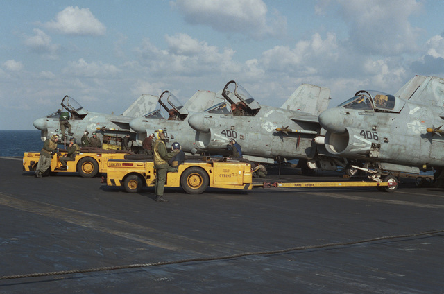 A-7E Corsair II aircraft are serviced on the flight deck of the aircraft carrier USS SARATOGA (CV 60) during operations off the coast of Libya. Crewmen are standing by to move the aircraft with MD-3A tow tractors