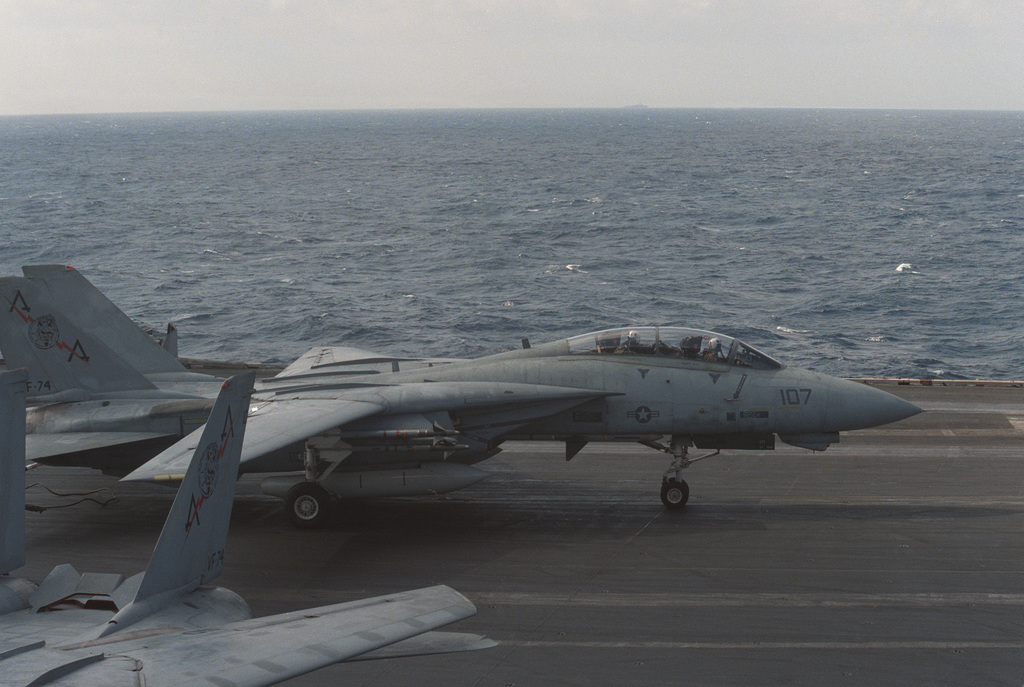An F-14A Tomcat aircraft lands aboard the aircraft carrier USS SARATOGA (CV 60) during flight operations off the coast of Libya. The aircraft is armed with AIM-9 Sidewinder missiles on the wing and an AIM-7 Sparrow missile on the fuselage
