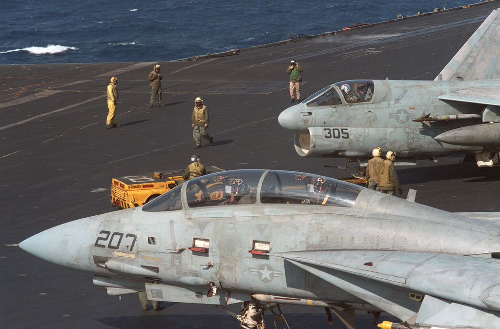 An F-14A Tomcat, foreground, and A-7E Corsair II aircraft are prepared for flight operations aboard the aircraft carrier USS SARATOGA (CV 60) during operations off the coast of Libya
