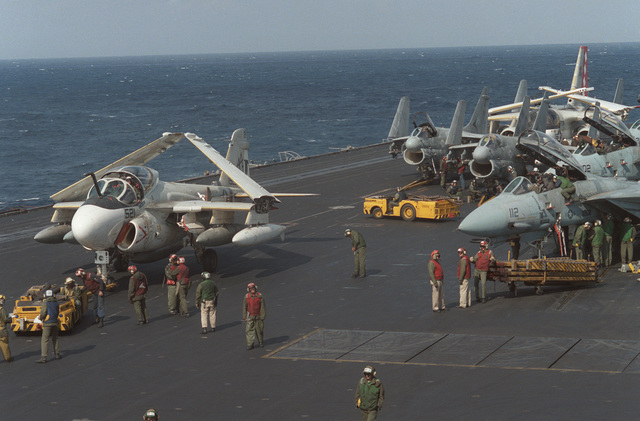 An MD-3A tow tractor is used to maneuver an A-6E Intruder aircraft, left, on the flight deck of the aircraft carrier USS SARATOGA (CV 60) during operations off the coast of Libya. On the right are F-14A Tomcat aircraft and in the center background are A-7E Corsair II aircraft