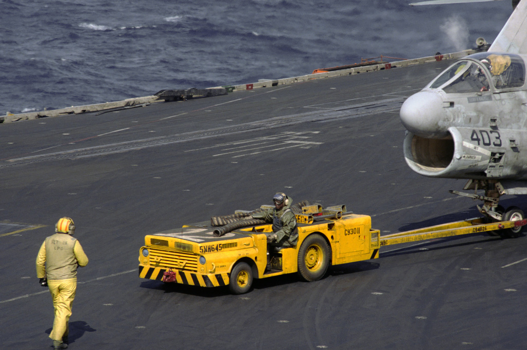 An MD-3A tow tractor pulls an A-7E Corsair across the flight deck of the aircraft carrier USS SARATOGA (CV 60) during operations off the coast of Libya
