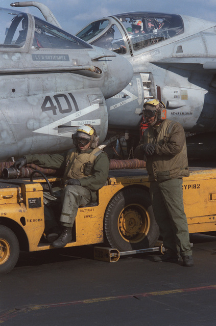 Flight deck crewmen aboard the aircraft carrier USS SARATOGA (CV 60) prepare to move an A-7E Corsair II aircraft with an MD-3A tow tractor during operations off the coast of Libya