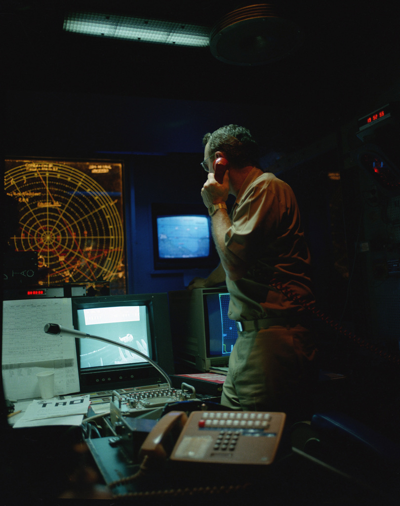 Rear Admiral David E. Jeremiah, commander, Task Force 60, uses a telephone in the task force command and control room of the aircraft carrier USS SARATOGA (CV 60) during operations off the coast of Libya