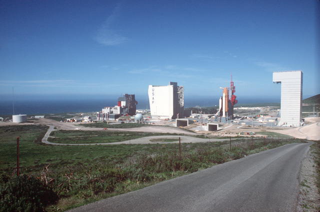 The space shuttle Enterprise, mated to an external tank and solid rocket boosters, rests on the launch mount next to the access tower at Space Launch Complex Six. On the far right is the mobile service tower and on the left are the payload preparation room, payload changeout room and the shuttle assembly building (marked USAF)