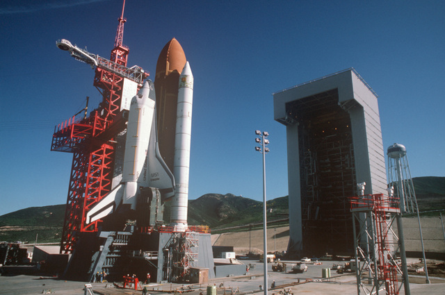 The space shuttle Enterprise, mated to an external tank and solid rocket boosters, rests on the launch mount next to the access tower at Space Launch Complex Six.  On the right is the mobile service tower