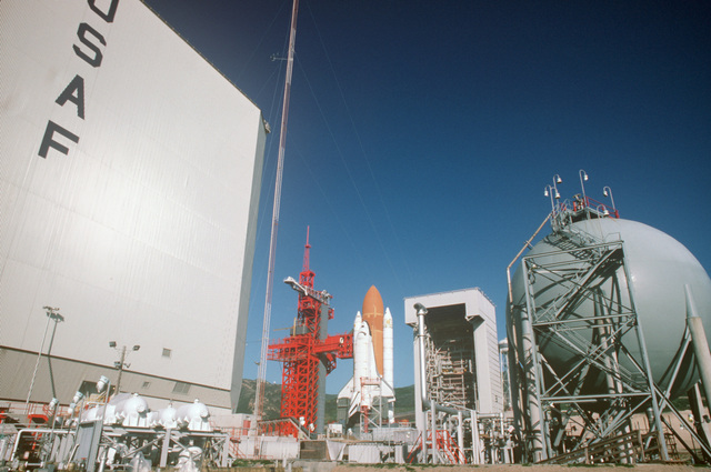 The space shuttle Enterprise, mated to an external tank and solid rocket boosters, rests on the launch mount next to the access tower at Space Launch Complex Six.  In the background is the mobile service tower and in the left foreground is a portion of the shuttle assembly building