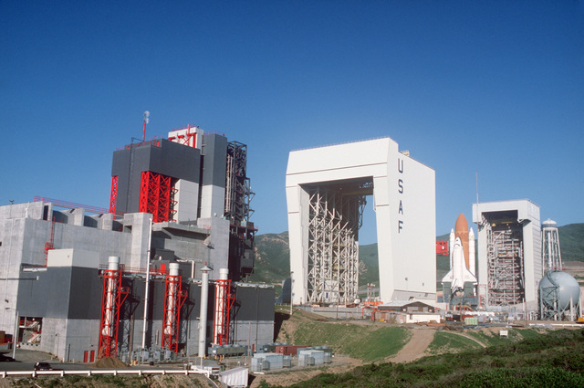 The space shuttle Enterprise, mated to an external tank and solid rocket boosters, rests on the launch mount at Space Launch Complex Six. On the far right is the mobile service tower and on the left are the payload preparation room, payload changeout room and the shuttle assembly building (marked USAF)
