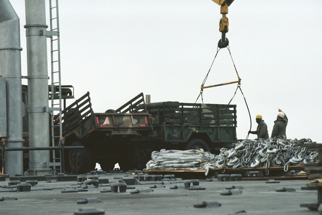 Workers attach a sling to a utility trailer parked on the deck of the vehicle cargo/rapid response ship USNS ANTARES (T-AKR 294) during offloading operations at the Dundalk Marine Terminal. The trailer was used by the 32nd Separate Infantry Brigade (Mechanized), Wisconsin Army National Guard, during Exercise REFORGER '86