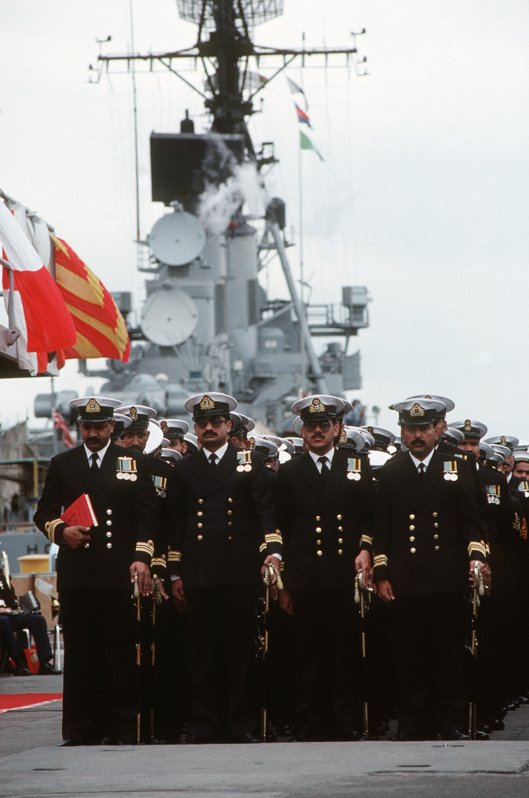 Pakistani officers stand in formation during the commissioning ceremony of the former Guided Missile Frigate USS BROOKE (FFG 1) as the ship is transferred to the Pakistani navy and assumes the name PNS KHAIBAR (D 163).  The former frigate USS O'CALLAHAN (FF 1051) is also being transferred and assuming the name PNS ASLAT (F 265)