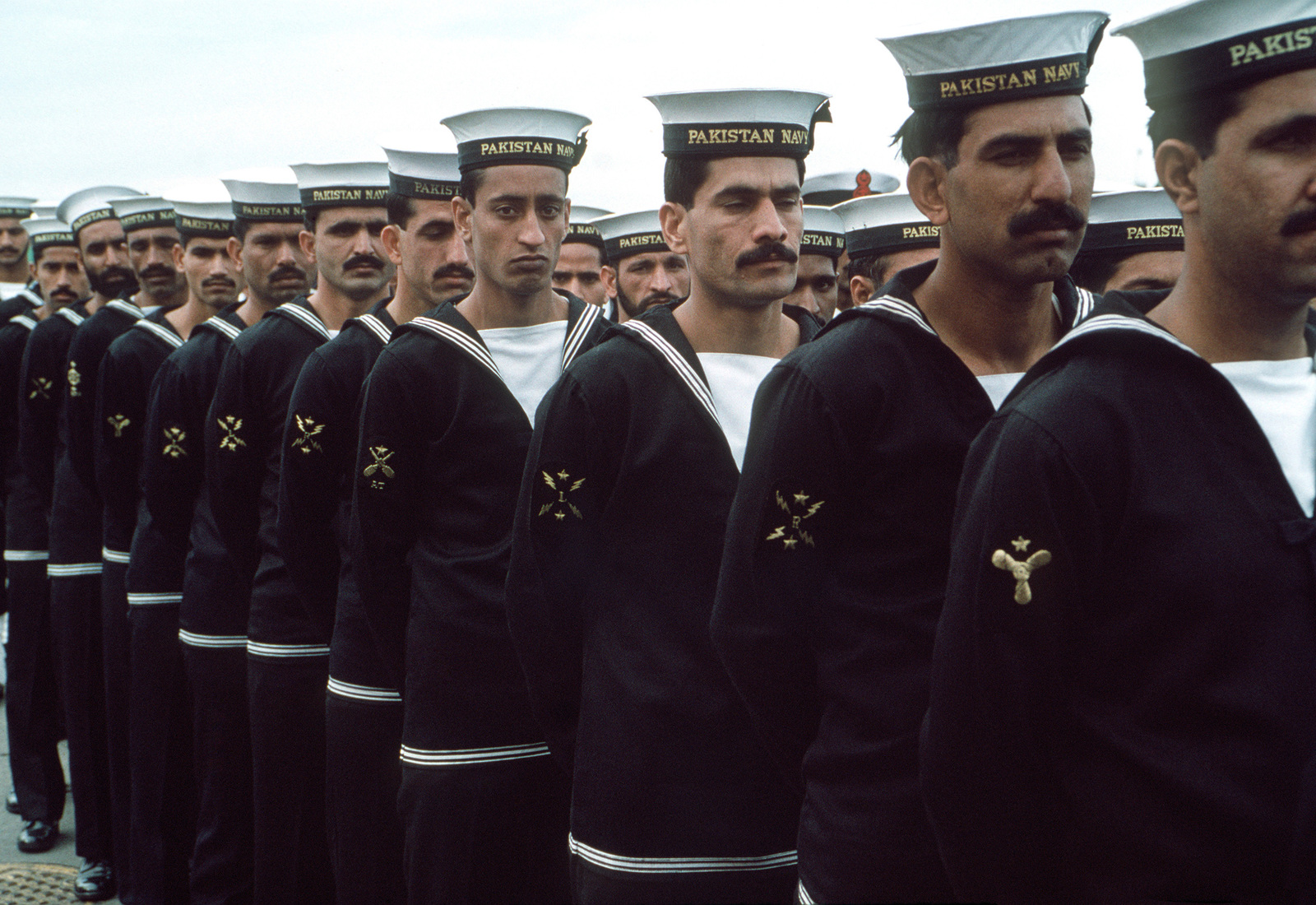 Pakistani Sailors stand in formation during the commissioning ceremony by which the former Guided Missile Frigate USS BROOKE (FFG 1) and the former Frigate USS O'CALLAHAN (FF 1051) are transferred to the Pakistani navy.  The BROOKE is being commissioned PNS KHAIBAR (D 163) while the O'CALLAHAN becomes PNS ASLAT (F 265)