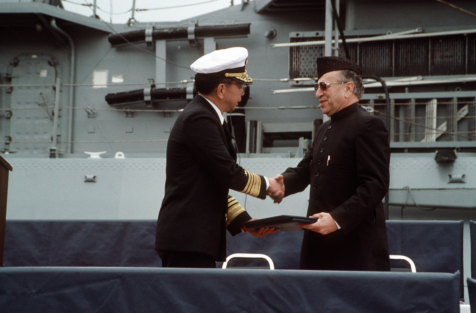 Vice Admiral (VADM) Robert K.U. Kihune, Commander, Naval Surface Force, US Pacific Fleet, presents transfer documents to Jamsheed K.A. Marker, Ambassador of Pakistan, at the conclusion of the commissioning ceremony by which the former Guided Missile Frigate USS BROOKE (FFG 1) and the former frigate USS O'CALLAHAN (FF 1051) were transferred to the Pakistani navy.  The BROOKE was commissioned PNS KHAIBAR (D 163) while the O'CALLAHAN became PNS ASLAT (F 265)