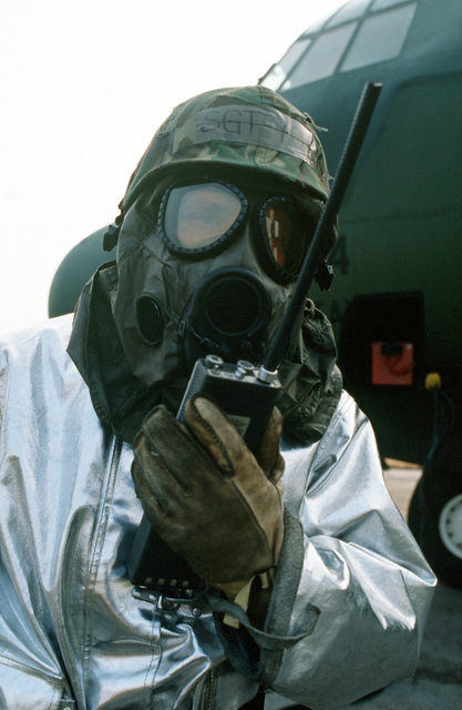 A fireman, wearing a proximity suit and an M-17 nuclear-biological-chemical warfare mask, uses a field radio to communicate information during exercise Bluetail maneuvers. The exercise is designed to test the operational readiness of the 435th Tactical Airlift Wing and wing tenant organizations