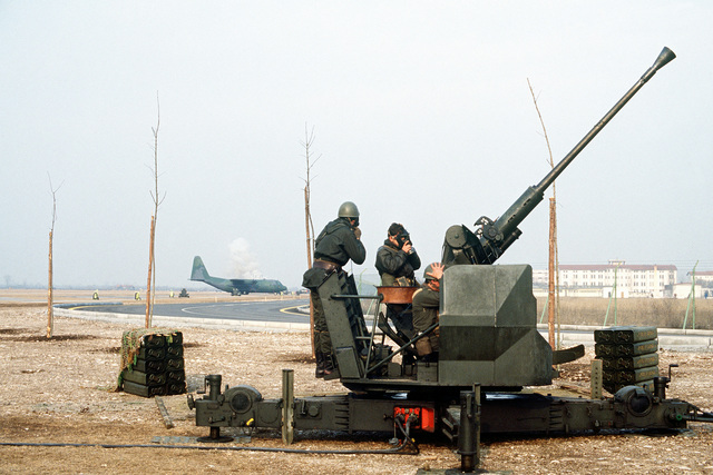 Members of Italy's 21st Artillery Group, Anti-aircraft Battery, secure their gas masks prior to firing a 40mm L/70 anti-aircraft gun. The Italian military personnel are participating in exercise Bluetail maneuvers, designed to test the operational readiness of the 435th Tactical Airlift Wing and wing tenant organizations