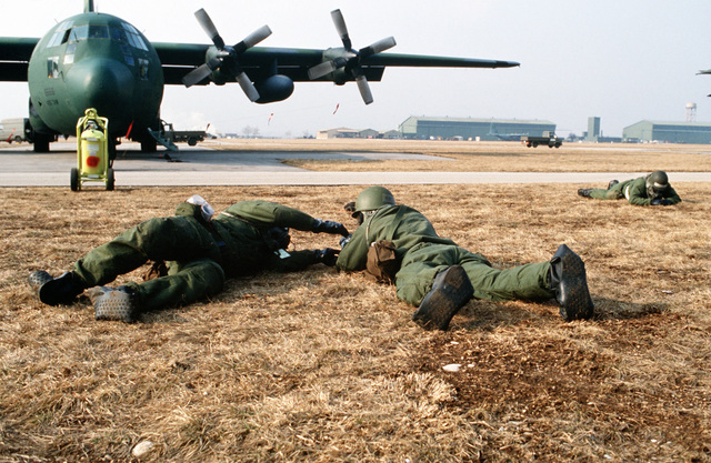 Members of the 435th Tactical Air Wing (435th TAW) act as casualties after a simulated attack near a 37th Tactical Airlift Squadron C-130E Hercules aircraft. The airmen, equipped with nuclear-biological-chemical warfare gear, are taking part in exercise Bluetail maneuvers, designed to test the operational readiness of the 435th TAW and wing tenant organizations