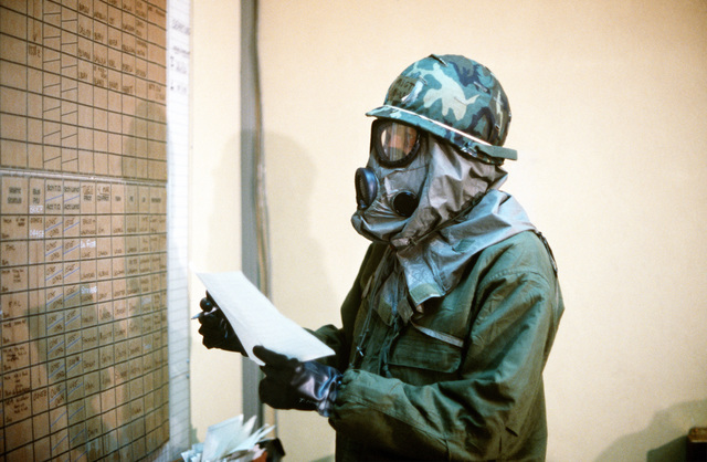MSGT Cowley, 37th Tactical Airlift Squadron, checks an assignment chart during exercise Bluetail maneuvers, designed to test the operational readiness of the 435th Tactical Airlift Wing and wing tenant organizations. Cowley is wearing an M-17 nuclear-biological-chemical warfare mask