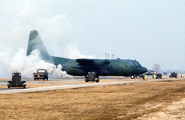 Smoke pours from smoke grenades near a 37th Tactical Airlift Squadron C-130E Hercules aircraft during a simulated attack, part of exercise Bluetail maneuvers, designed to test the operational readiness of the 435th Tactical Airlift Wing and wing tenant organizations