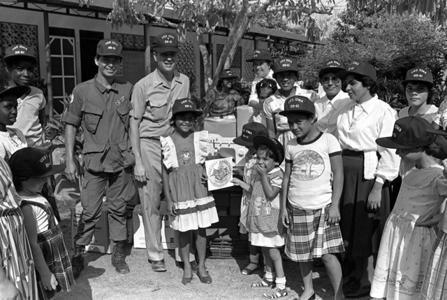 Chaplain (LT.) Thomas Murphy and another crew member from the battleship USS IOWA (BB-61) pose with Sister Teresita Rodriguez, mother superior, and other residents of the Hogar Cristiano Orphanage during a presentation of Projects Handclasp material. The project is part of a civic action project