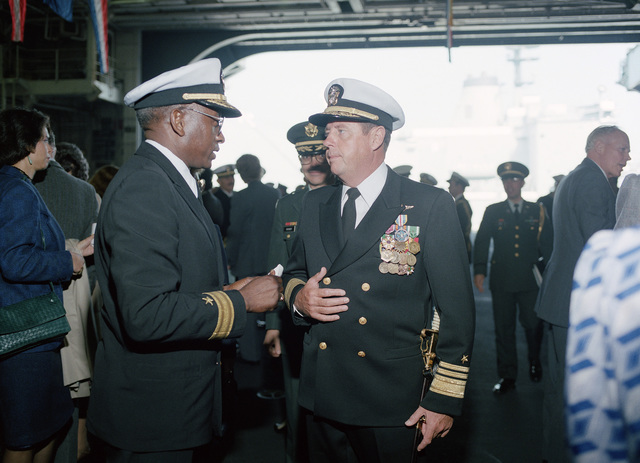Vice Admiral (VADM) Kendall E. Moranville, commander, Third Fleet, talks with Rear Admiral (RDML) (lower half Robert L. Toney, commander, Service Group One and Naval Base, San Francisco, during a change of command ceremony aboard the nuclear-powered aircraft carrier USS CARL VINSON (CVN 70). Rear Admiral (RADM) (upper half) John R. Batzler, commander, Carrier Group Three, is being relieved of duty by RDML (lower half) Edward W. Clexton Jr