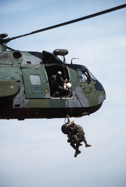 """A pararescueman and a""""survivor""""are hoisted aboard an HH-3E Jolly Green Giant helicopter during Exercise TEAM SPIRIT'86"""
