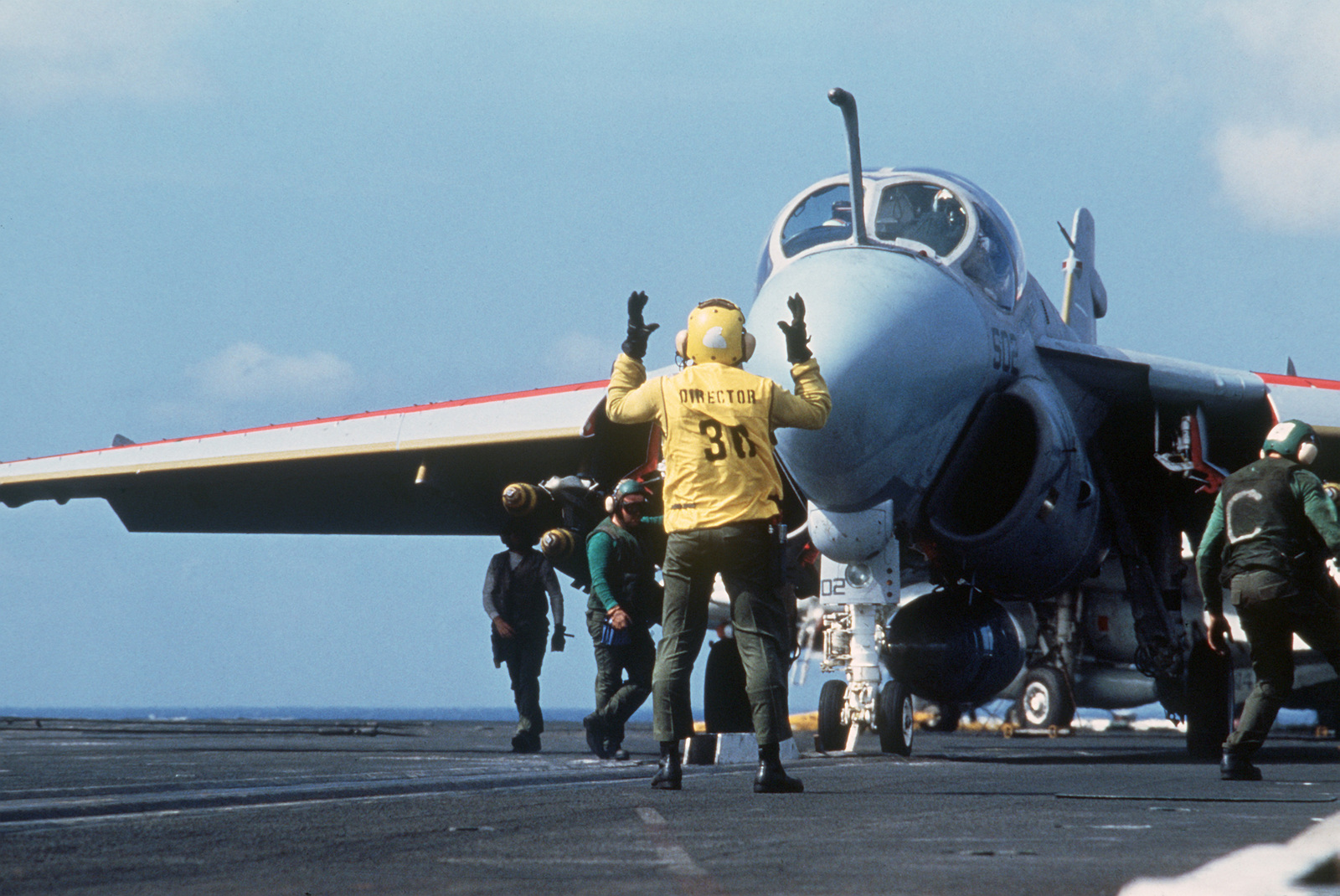 A plane director guides an A-6E Intruder aircraft into position on a catapult during flight operations aboard the nuclear-powered aircraft carrier USS ENTERPRISE (CVN 65)