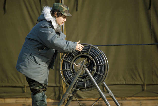 A US Air Force AIRMAN rolls out electrical cable during the constuction of a base camp for Exercise TEAM SPIRIT'86