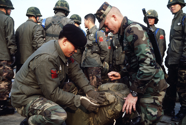 A US Army paratrooper helps a Korean counterpart ready his gear before an airdrop during Exercise TEAM SPIRIT'86